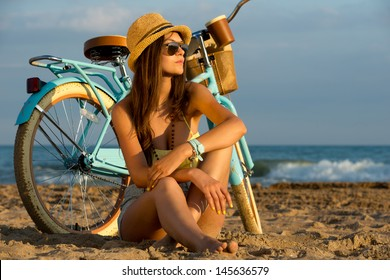 slender young brunette girl posing with a vintage bicycle on a background of the sea