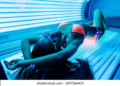 a slender young girl in a bathing suit sunbathing in a solarium, wants a beautiful tanned skin