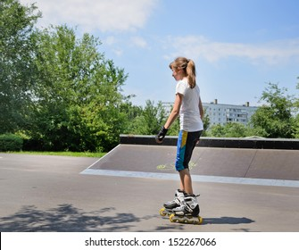 Slender young teenage girl on rollerblades in a skate park skating past a low cement ramp