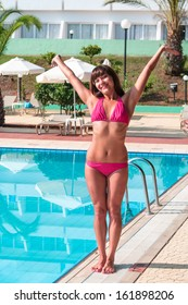 Slender young woman standing hands up behind swimming pool