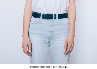 Slender young woman wearing blue high waist mom's jeans with belt and plain t-shirt standing over white background, close-up.
