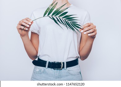 Slender young woman wearing blue high waist jeans with belt and plain t-shirt standing over white background holding green palm leaf, close-up.