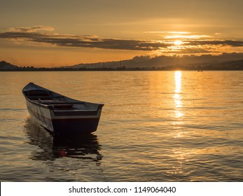 Slhouette of boat at the tropical sunset, view from beach on Ambon Island. Indonesia, Maluku, Maluki,