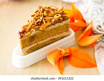 Slice of almond coffee cake on wood background