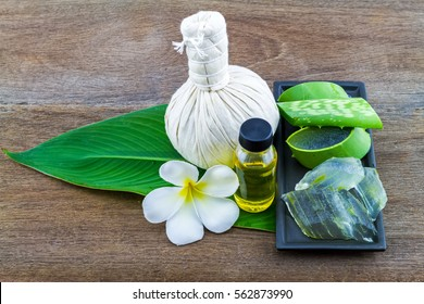 Slice Aloe Vera (Aloe barbadensis Mill.,Star cactus,  Aloin, Jafferabad or Barbados)  Spa compressing ball and Aloe vera essential oil in green leaf on wooden