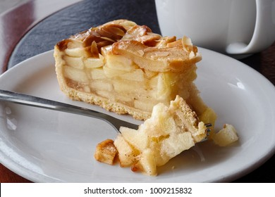 A slice of apple pie with pie on fork on white ceramic plate next to a fork. Black and brown table.
