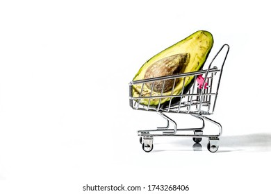 a slice of avocado lies in a toy grocery cart on a white background