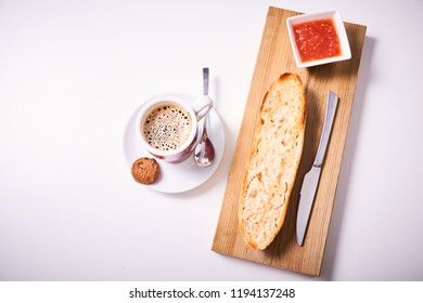 Slice of baguette on wooden table with strawberry jam and cup of coffee isolated on white background. Spanish breakfast.