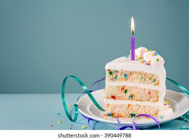 Slice Of Birthday Cake With A Lit Candle And Ribbons Over Blue Background