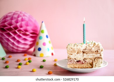 Slice of birthday cake on color background
