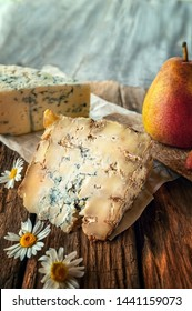 A slice of blue aged Stilton cheese on a wooden table. Cheese is served with a beautiful ripe pear. The quality of farmers ' agricultural products. Delicious English cheeses from Russian farmers