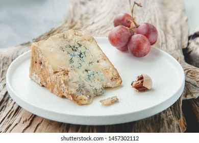 A slice of blue aged Stilton cheese on a wooden table. Cheese is served with large grapes. Quality of agricultural products of farmers. Delicious English cheeses from Russian farmers
