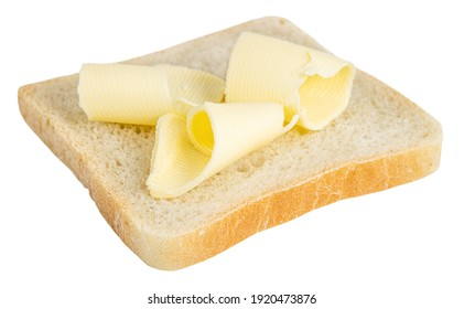 Slice of bread with butter curls on white background.