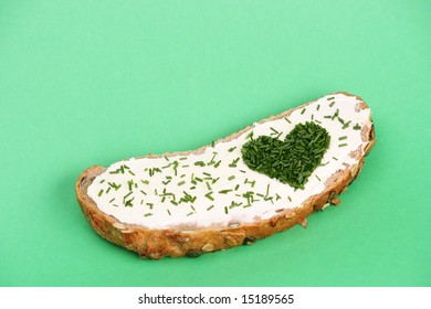 Slice of bread with butter and heart made of cut chive in shape of heart