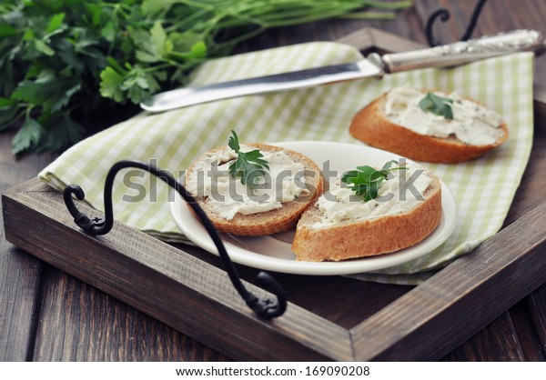 Slice of bread with cream cheese on vintage tray on wooden background