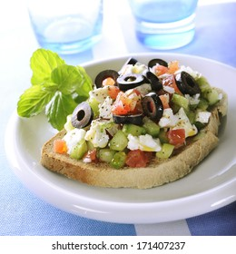 Slice of bread with mediterranean topping, feta, olives and tomato