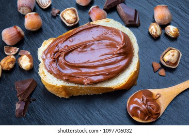 Slice of bread with spread chocolate cream and hazelnuts on black table. Serving a delicious breakfast concept.