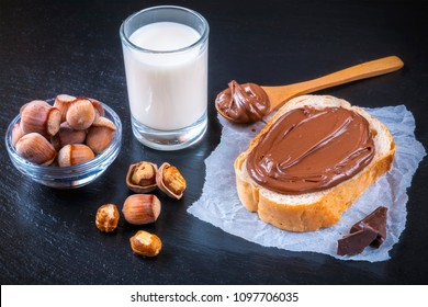 Slice of bread with spread chocolate cream and hazelnuts on black table. Serving a delicious breakfast concept. Focus on hazelnut in bowl.
