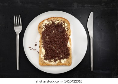Slice of brown bread with chocolate sprinkles -or in Dutch hagelslag- on white plate, stainless steel silverware and black stone background.