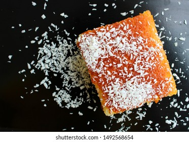 slice of cake with coconut powder in the plate, semolina dessert, top view