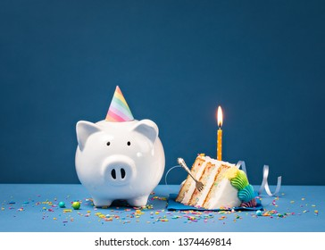 Slice of Cake with one Candle and Piggy Bank over a blue background. Birthday Money Concept.
