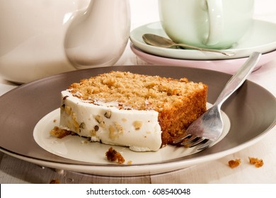 slice carrot cake on a plate with fork, cut and teapot