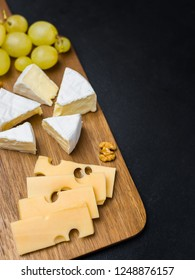 Slice of cheese, nuts and grapes on wooden cutting board. Camembert cheese and edam cheese. Food for wine and romantic. Top view image with copy space