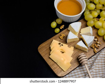 Slice of cheese, nuts, honey and grapes on wooden cutting board. Camembert cheese and edam cheese with plaid fabric. Food for wine and romantic