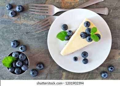 Slice of cheesecake with blueberries on a plate. Top view scene over a dark background.