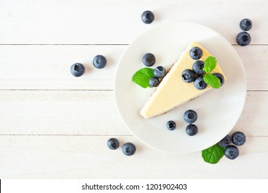 Slice of cheesecake with blueberries. Top view scene over a bright, white wood background.