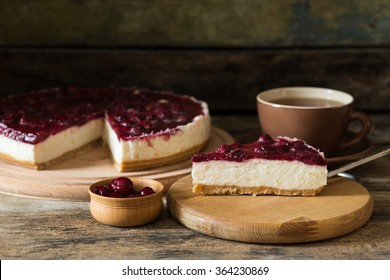 Slice of cheesecake with cherry and cup of tea on wooden background