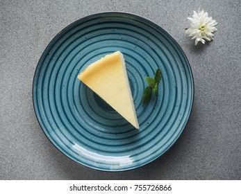 Slice of Cheesecake on blue plate on grey background