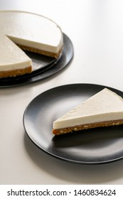 A slice of cheesecake on a gray plate on a white table against the background of a dish with cheesecake. Vertical