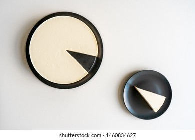 A slice of cheesecake on a gray plate and a dish with cheesecake on a white table turned to each other. View from above. Top