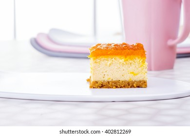 Slice of cheesecake  with oranges confiture jelly on white ceramic plate on the table and elegance pink cup of tea on white window background, New York Cheesecake