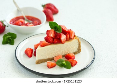 Slice of cheesecake with strawberries, mint and sauce. Selective focus
