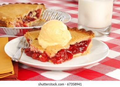 a slice of cherry pie topped with vanilla ice cream