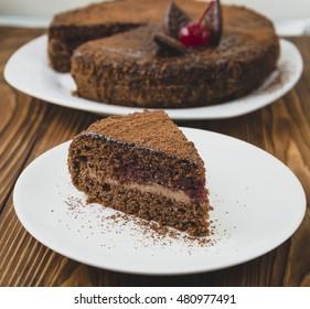 Slice of chocolate cake with cream and jam