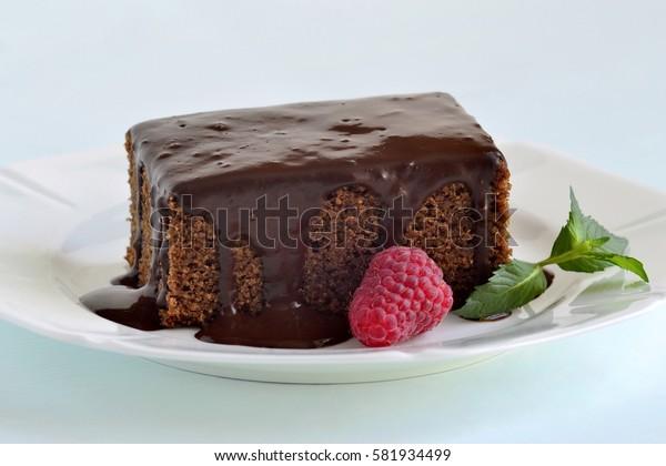 Slice of chocolate cake with glaze and raspberries, selective focus