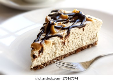 Slice of chocolate caramel cheesecake, in soft focus.