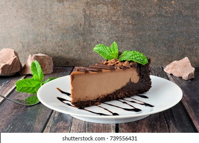 Slice of chocolate cheesecake on plate, still life with a rustic brown background