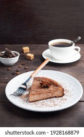 Slice of chocolate curd casserole on a plate, a portion piece of cake with chocolate and coffee. Dark wooden rustic background copy space