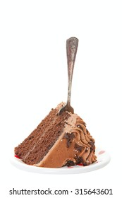 A slice of chocolate layer cake served on a plate with an antique fork in the middle.  Ready for eating.  Shot on white background.