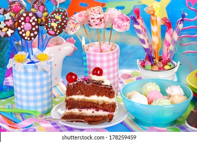 slice of chocolate torte with candle and homemade sweets for children birthday party
