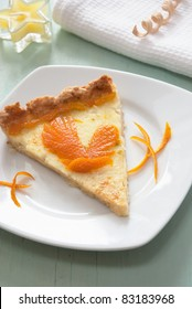 A slice of citrus pie with orange rind clipping like a bird