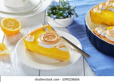 slice of Classic french lemon tart - crisp pastry with a smooth lemon filling decorated with meringue roses and edible fresh flowers, close-up