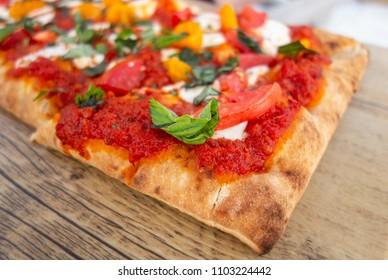 Slice of Classic Margherita Flatbread: Tomato Base, Fresh Mozzarella, Sliced Tomatoes, Basil on old rustic wood board, close up.