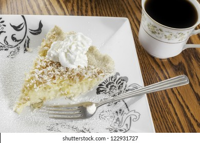 Slice of coconut cream pie with a cup of coffee