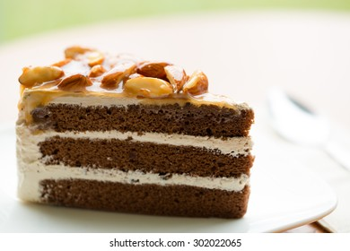 A Slice of Coffee Almond Cake on white plate, blurry background