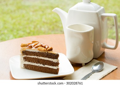 A Slice of Coffee Almond Cake on white plate with tea set